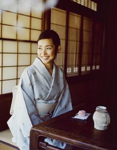 日本茶と和菓子を前にする和服の女性の写真素材 [FYI04076687]