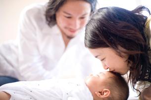 眠る赤ちゃんにキスする女性と男性の写真素材 [FYI04076690]