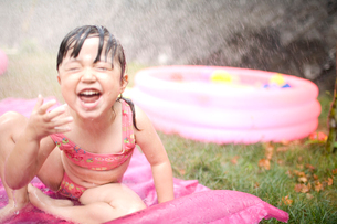 ビニールマットの上で水を浴びる女の子の写真素材 [FYI04076695]
