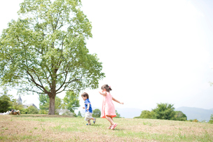 芝生を走る子供達の写真素材 [FYI04076730]