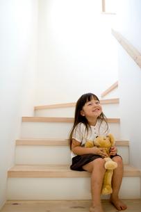 階段でぬいぐるみを持つ女の子の写真素材 [FYI04076751]