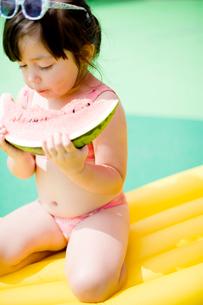 水着ですいかを食べる女の子の写真素材 [FYI04076765]