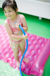 ホースで水をかける女の子の写真素材 [FYI04076769]