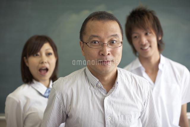黒板の前に立つ先生と生徒の写真素材 [FYI04078893]