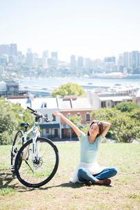 自転車の横で休んでいる女性の写真素材 [FYI04079678]