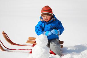 そりに乗って雪だるまを作る子供の写真素材 [FYI04082050]