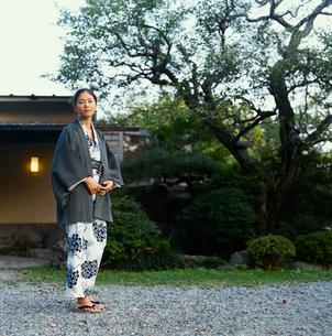 旅館の前に立つ浴衣姿の20代日本人女性の写真素材 [FYI04083109]
