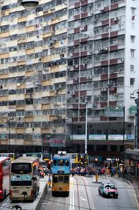 トランスフォーマーのロケ地にもなった香港はクウォリーベイのモンスターマンション海景楼前を走るトラムの写真素材 [FYI04083411]