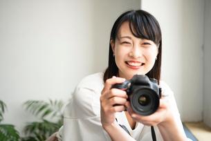 一眼レフカメラを構えて笑っている女性の写真素材 [FYI04083415]