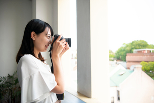 一眼レフカメラで写真を撮影している女性の写真素材 [FYI04083416]