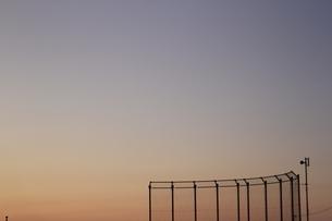 夕暮れ空とバックネットの写真素材 [FYI04083618]