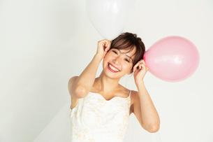 風船を持つウエディングドレス姿の20代花嫁の写真素材 [FYI04084947]