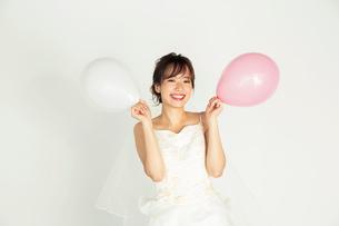 風船を持つウエディングドレス姿の20代花嫁の写真素材 [FYI04084948]