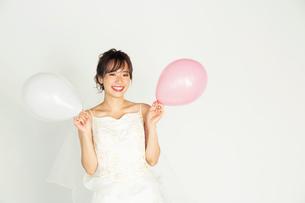 風船を持つウエディングドレス姿の20代花嫁の写真素材 [FYI04084949]