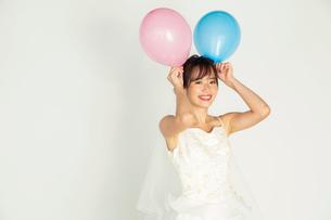 風船を持つウエディングドレス姿の20代花嫁の写真素材 [FYI04084950]