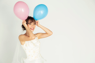風船を持つウエディングドレス姿の20代花嫁の写真素材 [FYI04084951]