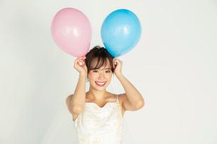風船を持つウエディングドレス姿の20代花嫁の写真素材 [FYI04084952]