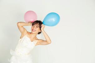 風船を持つウエディングドレス姿の20代花嫁の写真素材 [FYI04084953]
