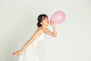 風船を持つウエディングドレス姿の20代花嫁の写真素材 [FYI04084955]