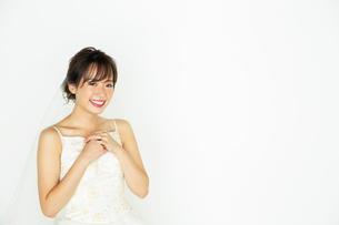胸に手を当てるウエディングドレスを着た20代花嫁の写真素材 [FYI04084973]