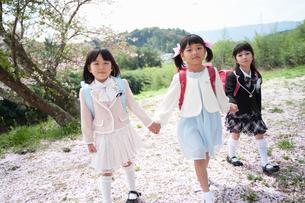 三人で並んで歩く正装した新一年生の女の子の写真素材 [FYI04085884]