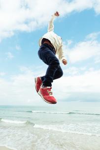 波打ち際でジャンプする男の子の写真素材 [FYI04085935]