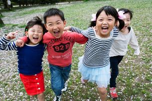 肩を組んで走る四人の子供たちの写真素材 [FYI04085938]