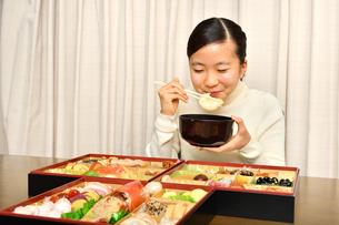 おせち料理を食べる女の子(正月)の写真素材 [FYI04087152]