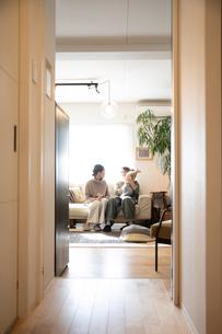 室内でくつろぐ3人家族の写真素材 [FYI04087194]