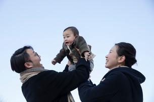 赤ちゃんを抱き上げる父親と母親の写真素材 [FYI04087206]