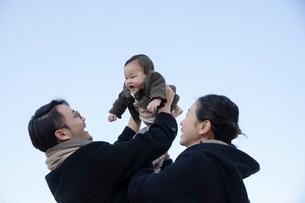 赤ちゃんを抱き上げる父親と母親の写真素材 [FYI04087207]