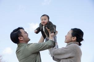 赤ちゃんを抱き上げる父親と母親の写真素材 [FYI04087211]