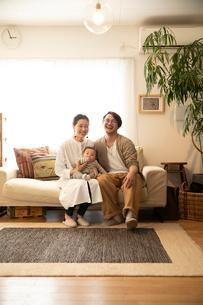 室内でくつろぐ3人家族の写真素材 [FYI04087357]
