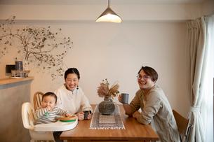 室内でくつろぐ3人家族の写真素材 [FYI04087359]
