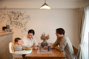 室内でくつろぐ3人家族の写真素材 [FYI04087360]