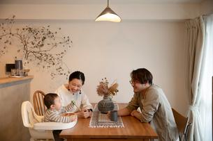 室内でくつろぐ3人家族の写真素材 [FYI04087361]