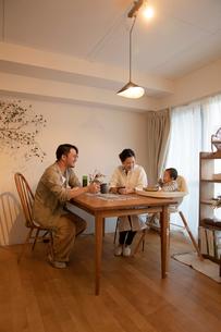 室内でくつろぐ3人家族の写真素材 [FYI04087365]