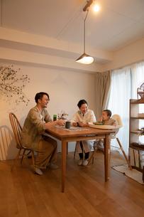 室内でくつろぐ3人家族の写真素材 [FYI04087366]