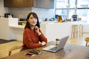 オフィスで遠くを見る日本人ビジネス女性の写真素材 [FYI04087425]