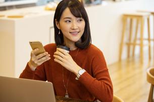 コーヒーを持つ日本人ビジネス女性の写真素材 [FYI04087431]
