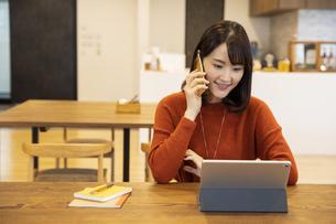 スマートフォンで通話する日本人ビジネス女性の写真素材 [FYI04087435]