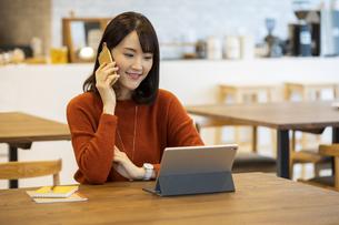 スマートフォンで通話する日本人ビジネス女性の写真素材 [FYI04087436]