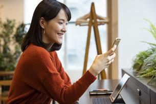 スマートフォンを見る日本人ビジネス女性の写真素材 [FYI04087448]