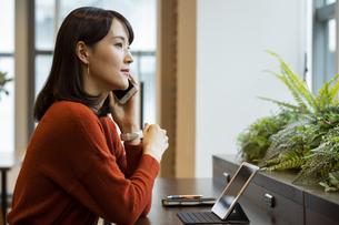 スマートフォンで通話する日本人ビジネス女性の写真素材 [FYI04087450]