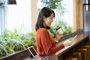 コーヒーを持つ日本人ビジネス女性の写真素材 [FYI04087452]