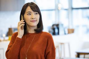スマートフォンで通話する日本人ビジネス女性の写真素材 [FYI04087454]