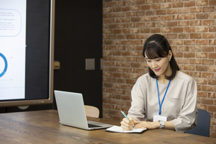 スケジュールを確認する日本人ビジネス女性の写真素材 [FYI04087455]