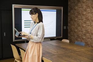 タブレットPCを操作する日本人ビジネス女性の写真素材 [FYI04087461]