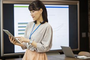 タブレットPCを操作する日本人ビジネス女性の写真素材 [FYI04087463]