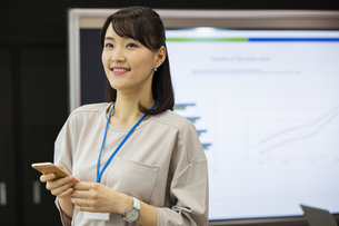 スマートフォンを操作する日本人ビジネス女性の写真素材 [FYI04087468]